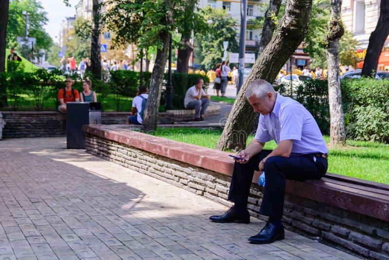 KIEV, UCRÂNIA - 20 DE JUNHO DE 2018: equipe texting com seu telefone celular, ele está sentando-se em um banco de madeira foto de stock royalty free