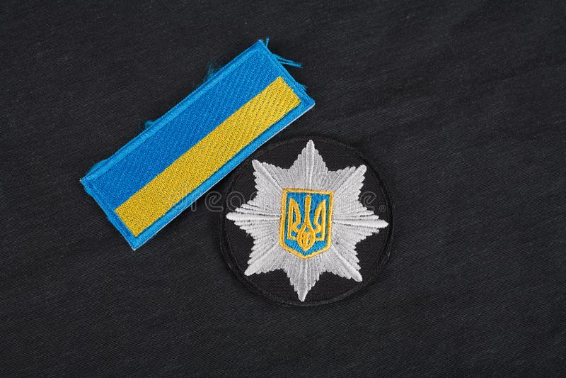 KIEV, UCRÂNIA - 22 DE NOVEMBRO DE 2016 Remendo e crachá da polícia nacional de Ucrânia no fundo uniforme preto imagens de stock royalty free