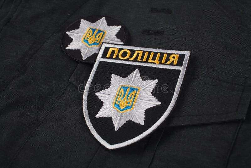 KIEV, UCRÂNIA - 22 DE NOVEMBRO DE 2016 Remendo e crachá da polícia nacional de Ucrânia no fundo uniforme preto fotografia de stock royalty free