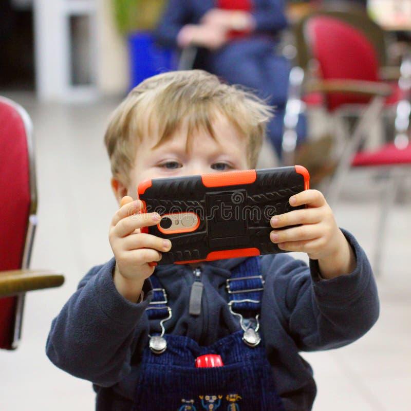 Kiev, Ucraina - 19 aprile 2018: Il ragazzino sta giocando sul telefono fotografie stock