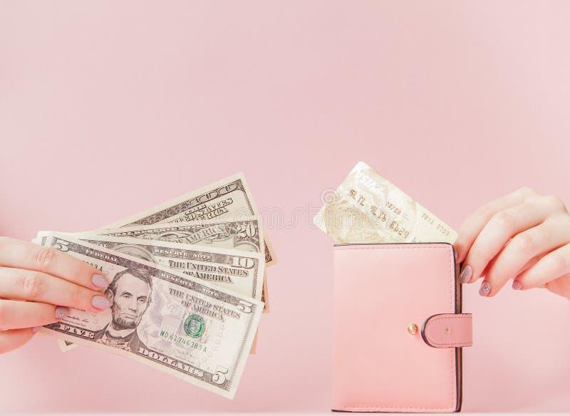 Kiev, Ucraina - 22 febbraio 2019: Dollari e portafoglio rosa con la carta di credito in mani della donna su fondo rosa immagini stock libere da diritti