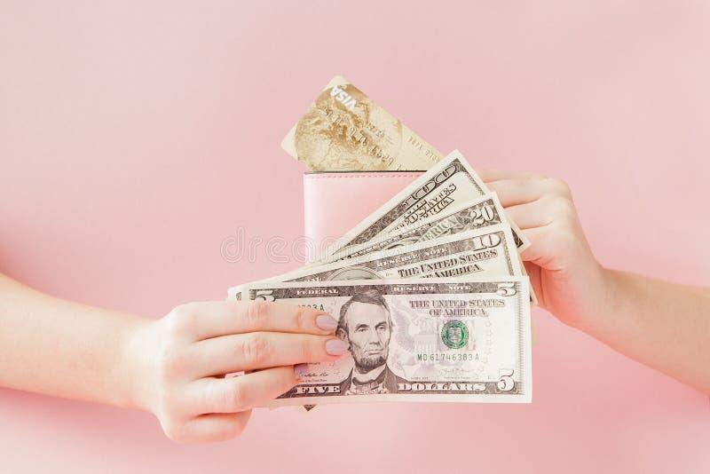 Kiev, Ucraina - 22 febbraio 2019: Dollari e portafoglio rosa con la carta di credito in mani della donna su fondo rosa fotografia stock libera da diritti