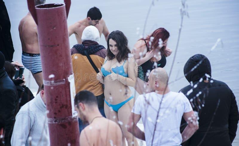 Kiev, Ucraina - gennaio 19, 2017: I cristiani ortodossi celebrano l'epifania con nuoto del ghiaccio ragazza che mostra il ` della fotografia stock libera da diritti