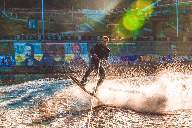 Kiev, Ucraina 31 03 2019 Il tipo in un thermosuit guida un bordo sull'acqua nel fiume locale Sport moderno Wakeboarding fotografia stock libera da diritti