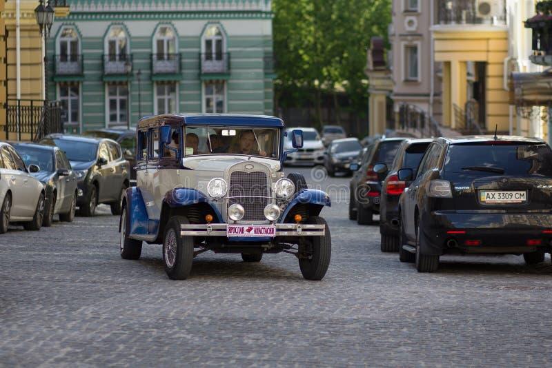 Kiev, Ucraina - 21 maggio 2016: Retro giri dell'automobile con le persone appena sposate fotografia stock libera da diritti