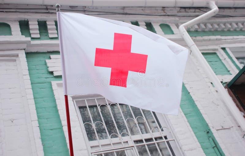 Kiev, Ucraina - 24 novembre 2016: Bandiera della croce rossa sulla costruzione antica L'organizzazione della croce rossa è un'org fotografia stock libera da diritti