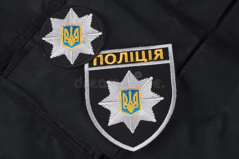 KIEV, UCRAINA - 22 NOVEMBRE 2016 La toppa ed il distintivo della polizia nazionale dell'Ucraina sul nero uniformano il fondo immagine stock