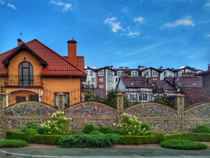 KIEV, UCRAINA - 25 settembre 2019: una bella casa privata con un prato e una bella recinzione contro un cielo azzurro fotografie stock libere da diritti