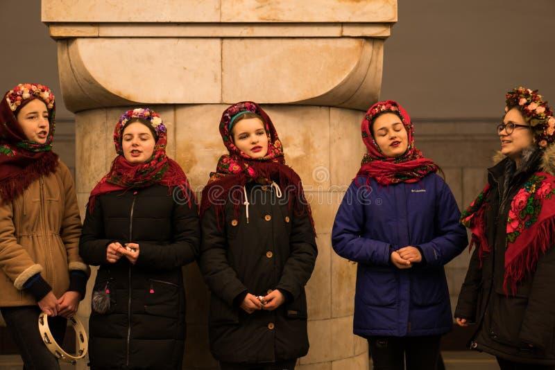 KIEV, UCRANIA - 14 DE ENERO: Las chicas jóvenes en desgaste étnico tradicional ucraniano están cantando villancicos en la estació fotos de archivo libres de regalías