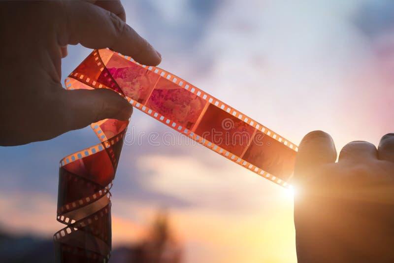 Kiev, Ucrania - 28 de junio de 2018: Un hombre con un fotonegativo en sus manos, por la tarde en la puesta del sol, memorias feli foto de archivo libre de regalías