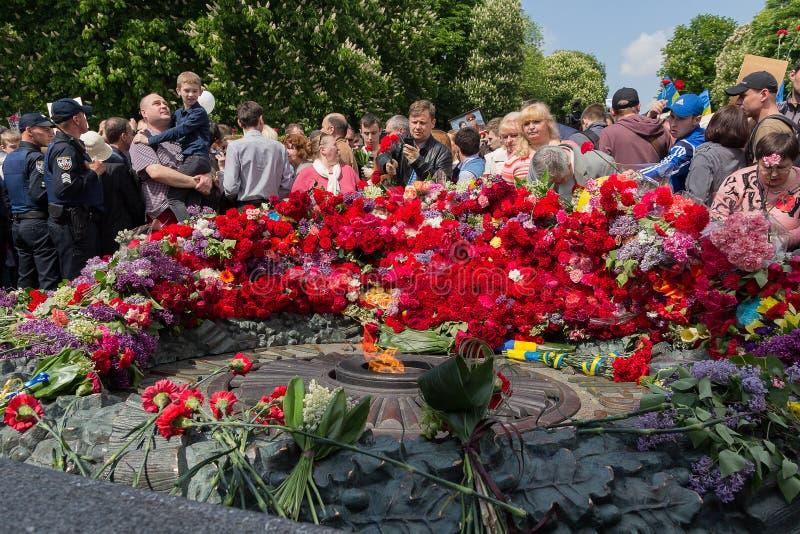 Kiev, Ucrania - 9 de mayo de 2016: Los ciudadanos ponen las flores al monumento a los soldados caidos foto de archivo libre de regalías