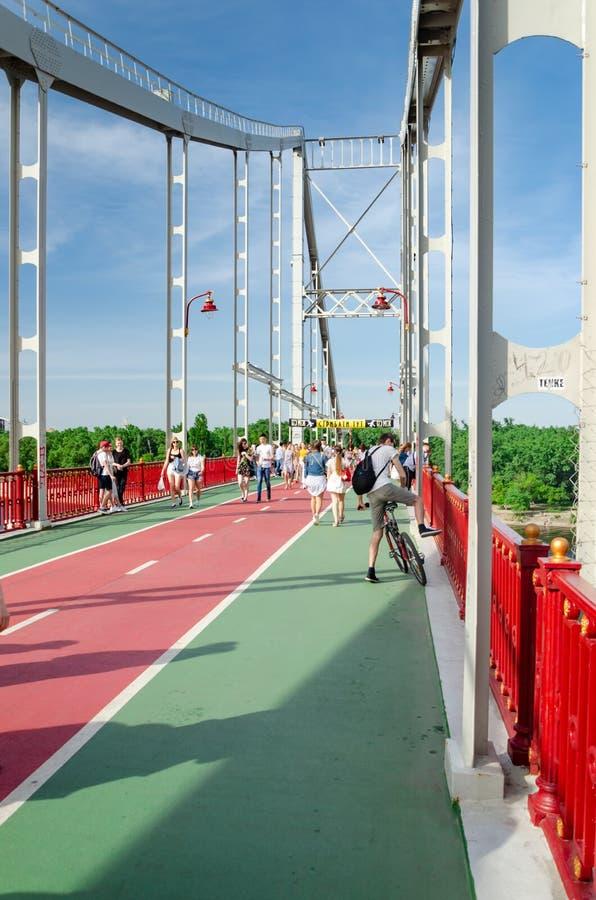 Kiev, Ucrania - 18 de mayo de 2019 Puente del parque sobre el r?o de Dnipro Gente que camina a lo largo del puente peatonal el fi fotografía de archivo libre de regalías