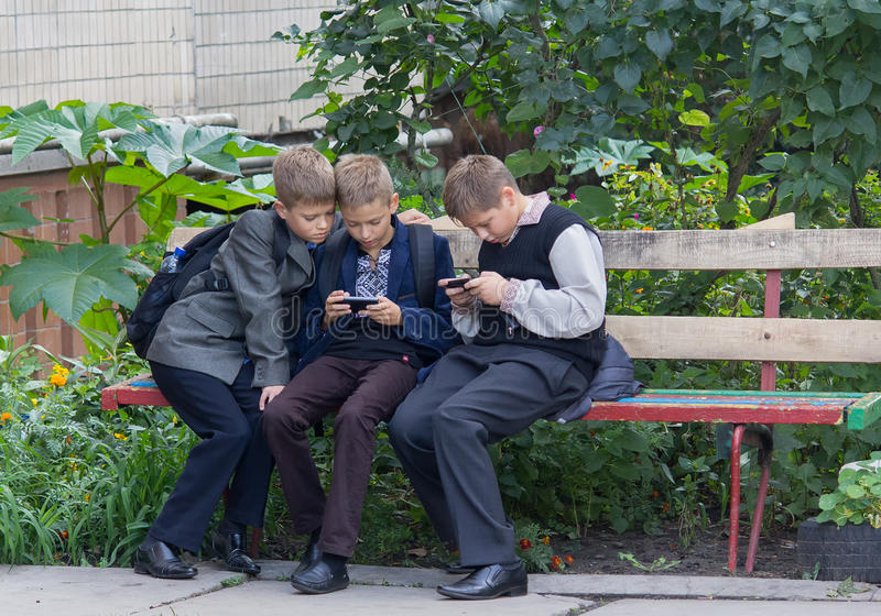 Kiev, Ucrania - 10 de septiembre de 2015: Los estudiantes que se sentaban en el banco jugaron con la ayuda de smartphones imagen de archivo