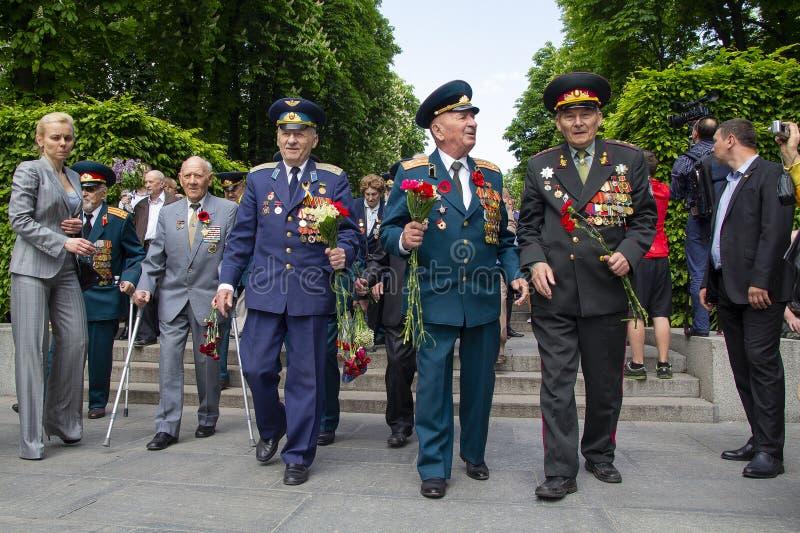Kiev, Ucrania - el 9 de mayo de 2016: Los veteranos de la Segunda Guerra Mundial ponen las flores en el parque de gloria eterna e foto de archivo libre de regalías