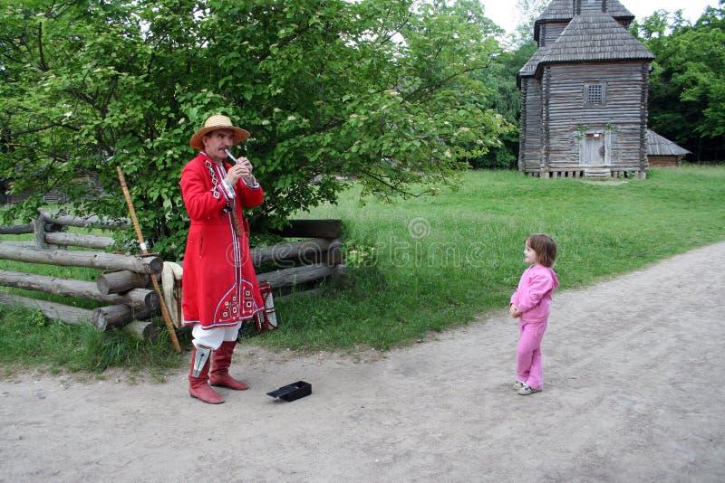 kiev ucrania 10 06 El músico 2006 de la calle está jugando en la flauta afuera La niña está escuchando él imágenes de archivo libres de regalías