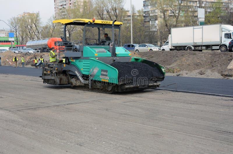 KIEV UKRAINA - APRIL 6, 2017: Arbetare som fungerar asfaltpaveren, bearbetar med maskin och tungt maskineri under vägreparationer arkivfoto