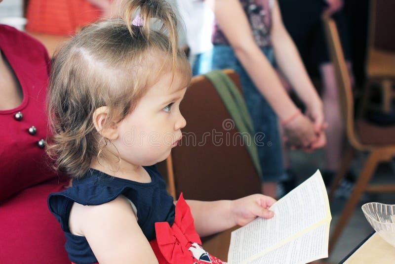 Kiev Ukraina - April 27, 2018: Lite sitter lyssnar flickan i en svart och en röd klänning, på hennes mammas varv och uppmärks royaltyfria foton