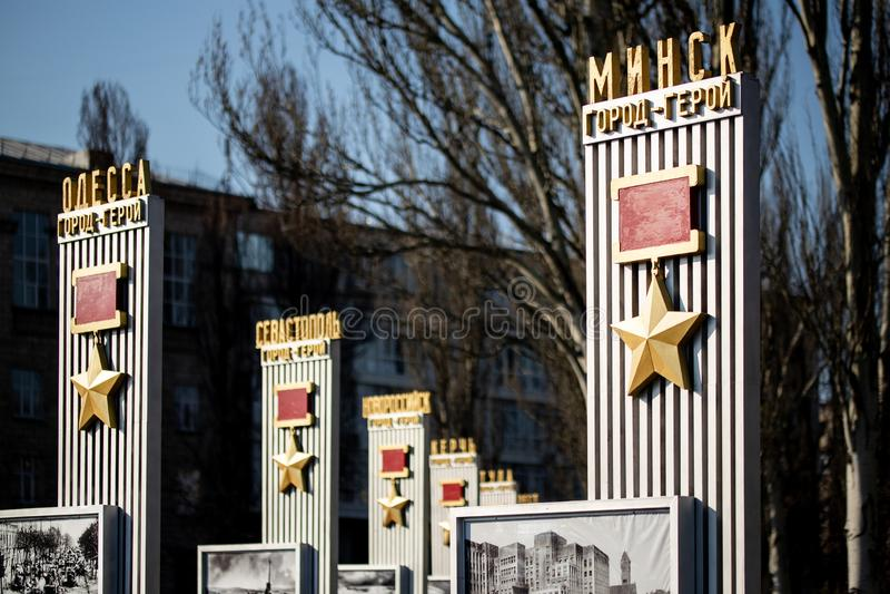 Kiev Ukraina - April 3rd, 2019: Minnes- gr?nd med monumentet med sovjetiska hj?ltestj?rnamedaljer till hj?lte-st?der av det stora royaltyfria foton