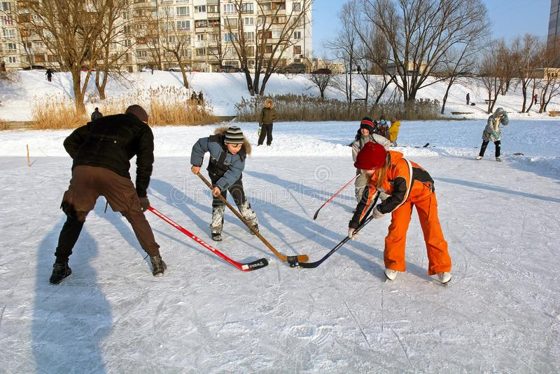 Kiev Ukraina, 19 02 2012 barn och en vuxen lekhockey på en åka skridskor isbana arkivfoto