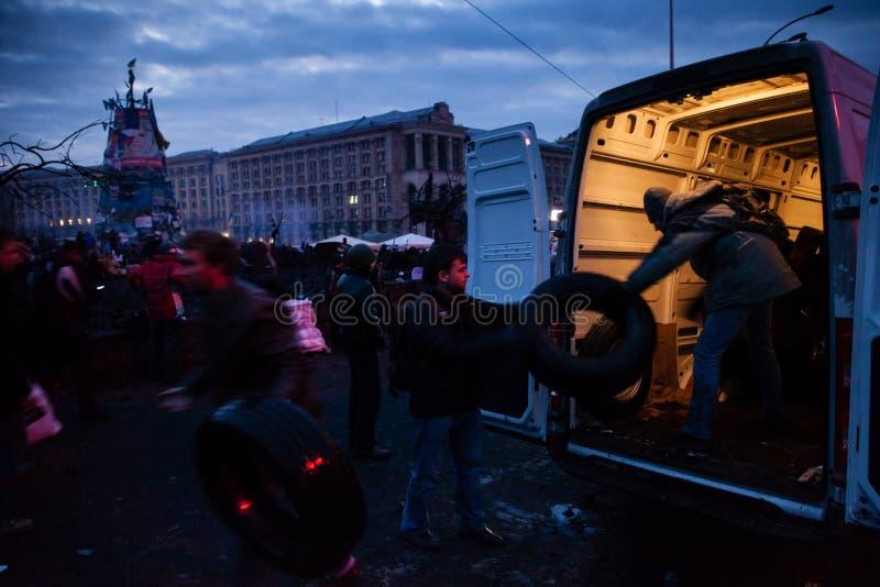 KIEV UKRAINA - Februari 20, 2014: Volontärer och aktivister av Euromaidan som kommer med gummihjul arkivfoto