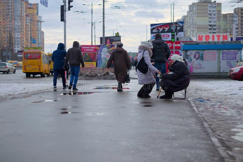 KIEV UKRAINA - JANUARI 29, 2018: En gammal hemlös kvinnatiggeri En fattig tiggeri för gammal kvinna på gatan royaltyfria bilder