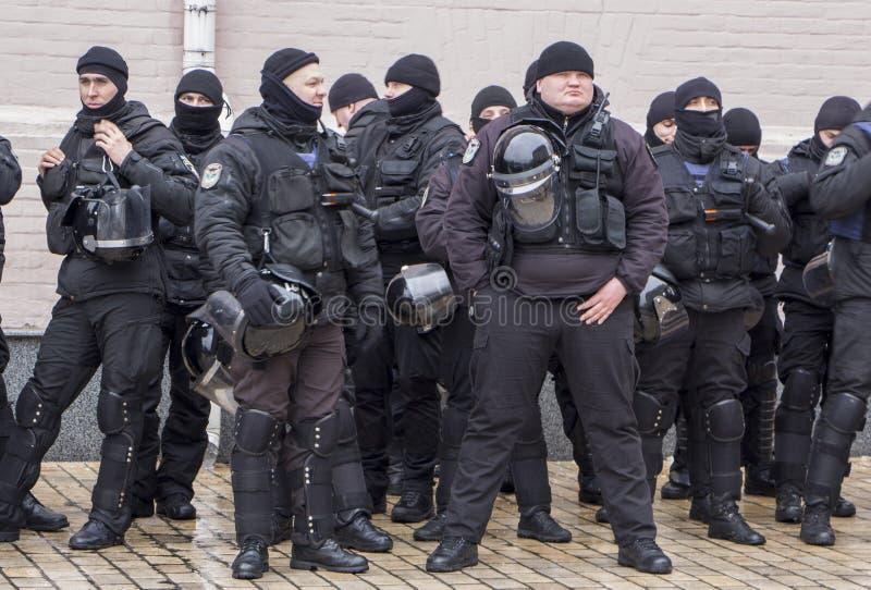 Kiev Ukraina - Januari 18th: Ukrainska poliser i svarta likformig på den Mikhailovskaya fyrkanten bevakar beställningen royaltyfri foto