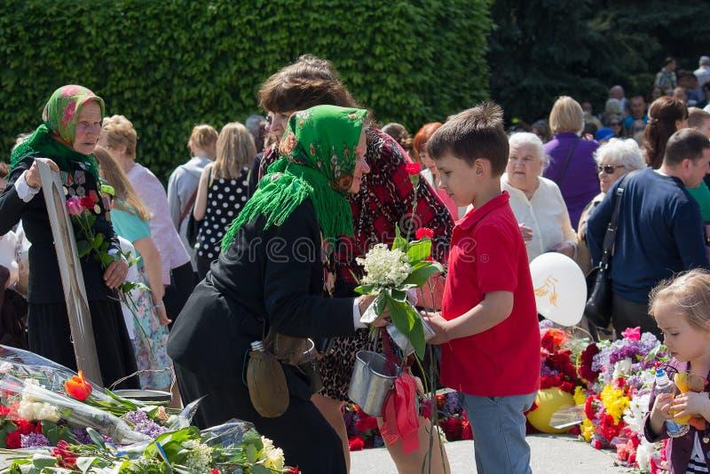 Kiev Ukraina - Maj 09, 2016: Pojke som ger blommor till hans farmor - en veteran av den andra världen Wa royaltyfri fotografi