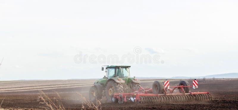 KIEV UKRAINA - MARS 27, 2019: Jordbruk traktor som förbereder land med såbäddodlaren som delen av pre att kärna ur aktiviteter in royaltyfria foton