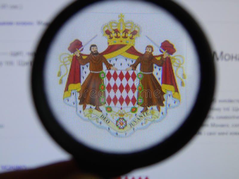 KIEV UKRAINA - MARS 23, 2019: Monaco vapensköld som beskådas till och med ett förstoringsglas royaltyfri illustrationer