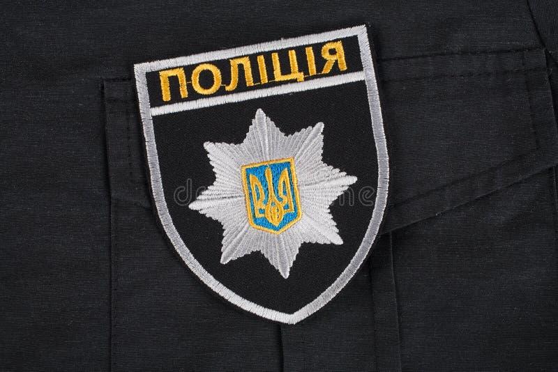 KIEV UKRAINA - NOVEMBER 22, 2016 Lappa och emblemet av nationella polisen av Ukraina på svart enhetlig bakgrund royaltyfri foto