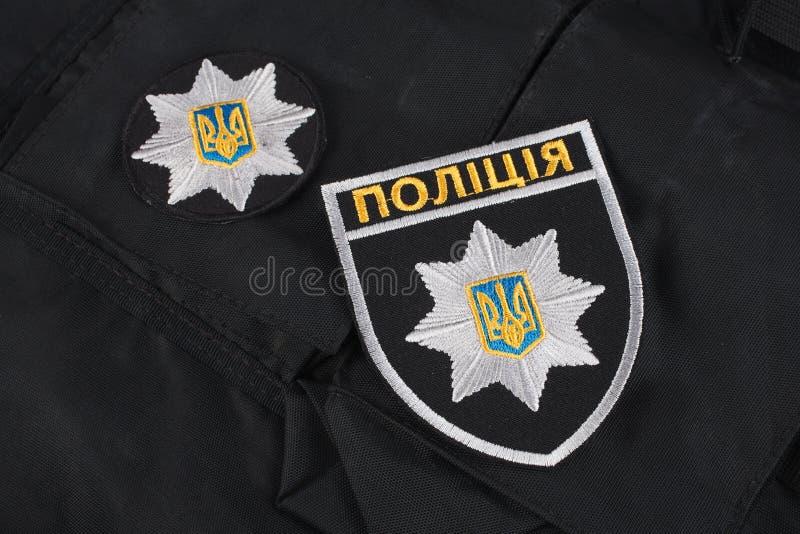 KIEV UKRAINA - NOVEMBER 22, 2016 Lappa och emblemet av nationella polisen av Ukraina på svart enhetlig bakgrund arkivbilder