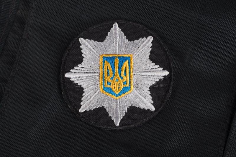 KIEV UKRAINA - NOVEMBER 22, 2016 Lappa och emblemet av nationella polisen av Ukraina på svart enhetlig bakgrund royaltyfri fotografi