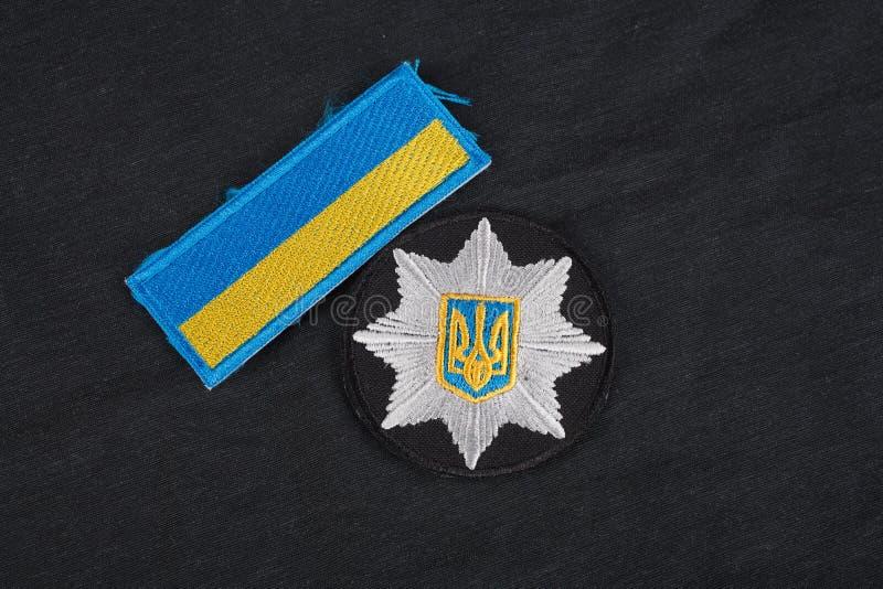 KIEV UKRAINA - NOVEMBER 22, 2016 Lappa och emblemet av nationella polisen av Ukraina på svart enhetlig bakgrund royaltyfria bilder