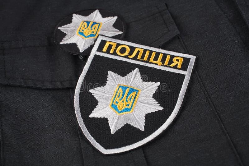 KIEV UKRAINA - NOVEMBER 22, 2016 Lappa och emblemet av nationella polisen av Ukraina på svart enhetlig bakgrund royaltyfri bild