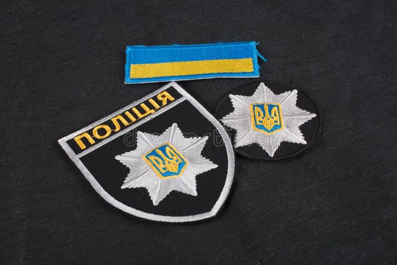 KIEV UKRAINA - NOVEMBER 22, 2016 Lappa och emblemet av nationella polisen av Ukraina på svart enhetlig bakgrund arkivbild