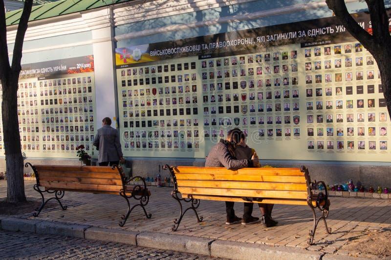 Kiev Ukraina - Oktober 14, 2018: Det unga paret sitter på en bänk nära gränden i minnet av soldaterna arkivfoto
