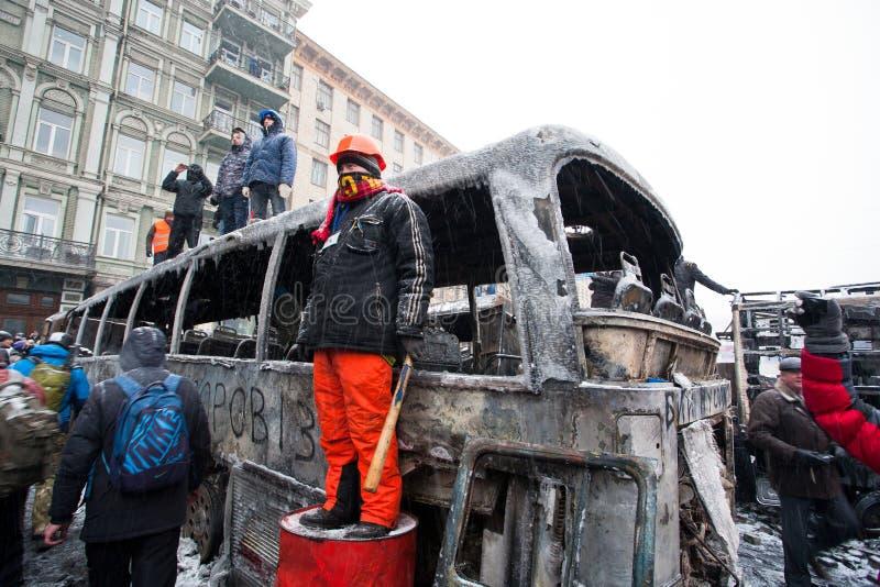 KIEV UKRAINA: Personen som protesterar med en taktpinne och en hjälm ser ut den brända gatan nära den stora brutna militära bilen royaltyfri fotografi
