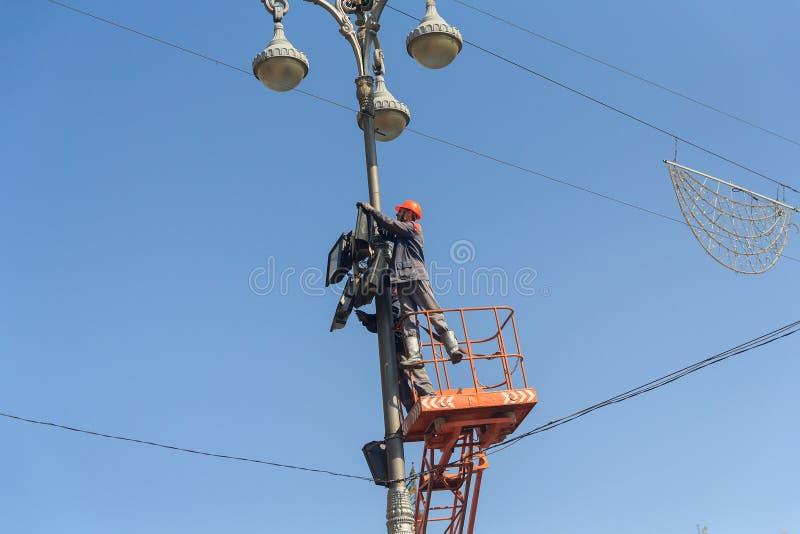 Kiev Ukraina - September 18, 2015: Elektriker som reparerar belysningsutrustning arkivfoton
