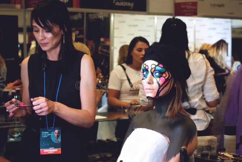 Kiev Ukraina – 19 September, 2018: Makeupkonstnären gör fantasikonstmakeup för ung modell på skönhetshowen arkivbild