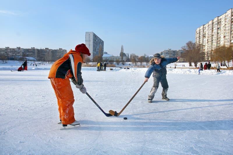 Kiev Ukraina, 19 02 2012 två barn på en isbana med hockeypinnar och en packningslekhockey arkivbild