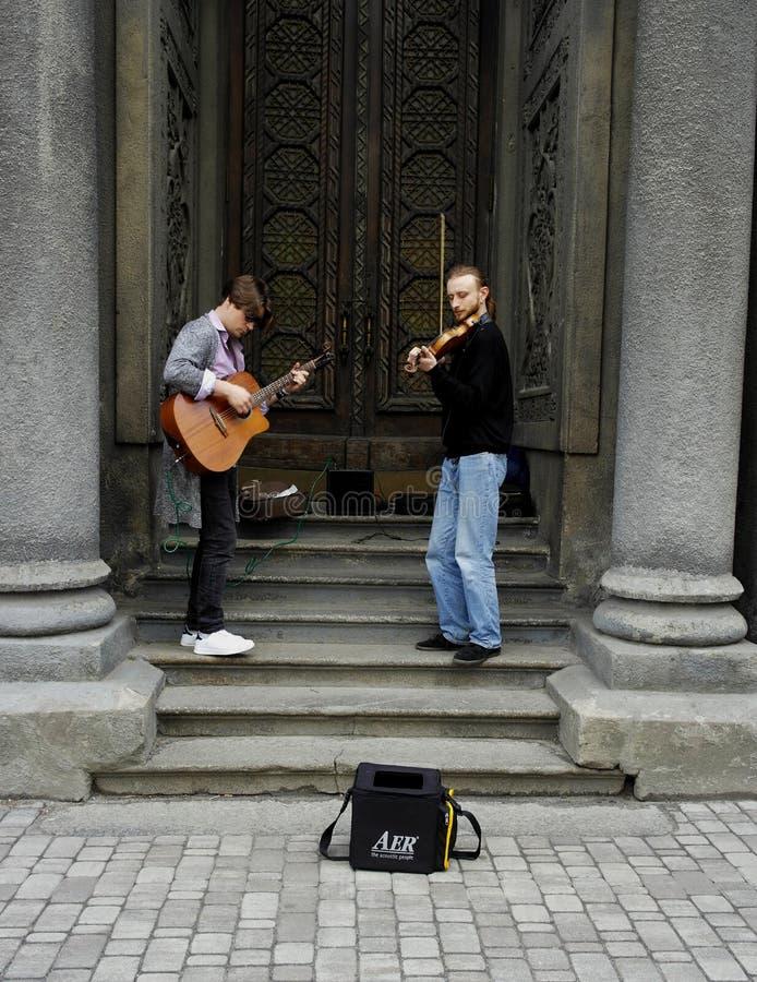 04 18 Kiev 2019 Ukraina Tv? gatamusiker En gitarrist och den andra violinisten på bakgrunden av dörrarna av synagen arkivbild