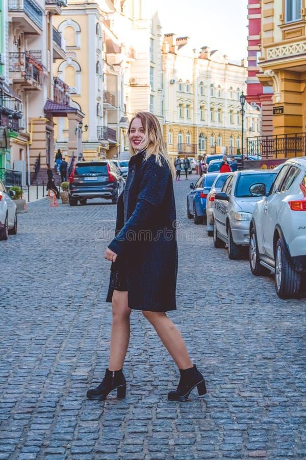 Kiev Ukraina 30 03 2019 Unga flickan i svart kläder i solig dag för vår går på gamla stadsgator Klänning, omslag och lag royaltyfri bild
