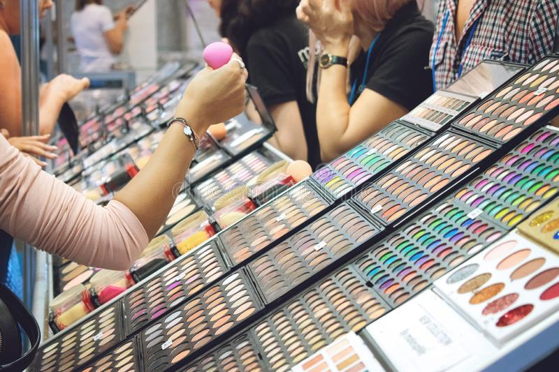Kiev, Ukraine 19 September, 2018: Young woman chooses decorative cosmetics at the beauty store stand during beauty show. Girl stock photo
