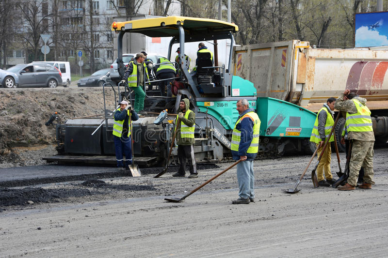 KIEV, UKRAINE - APRIL 6, 2017: Workers operating asphalt paver machine and heavy machinery during road repairs royalty free stock images
