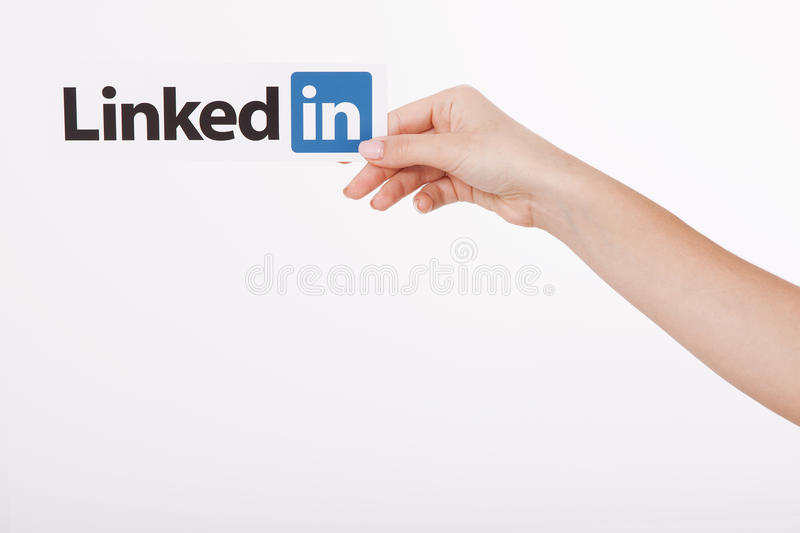 KIEV, UKRAINE - August 22, 2016: Woman hands holding Linkedin logo sign printed on paper on white background. Linkedin. Is a business social networking service stock image
