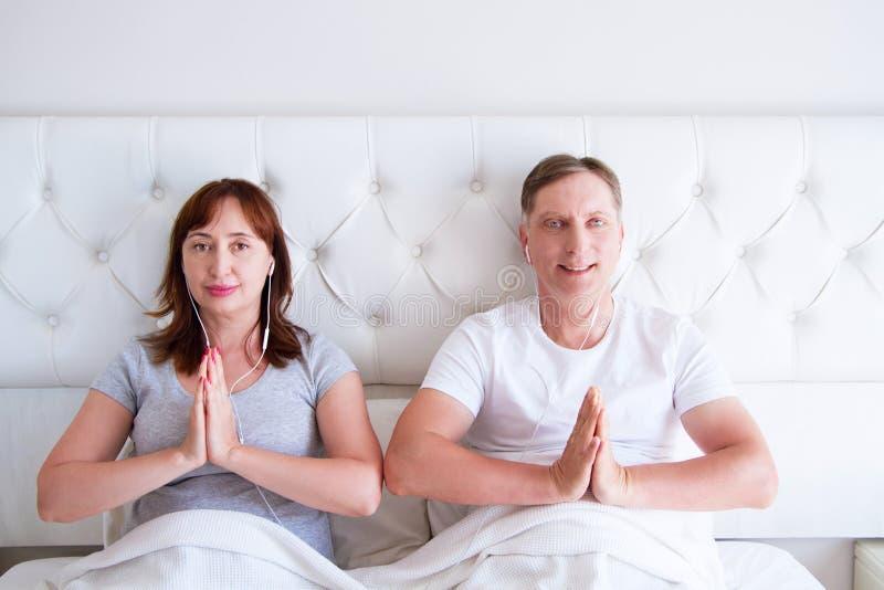 Kiev, Ukraine-09 10 2018: earpods de la manzana yoga, mindfulness, armonía y concepto de la gente - par de mediana edad feliz en  imagenes de archivo