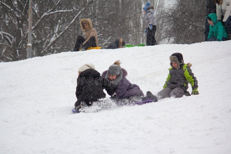 Kiev, Ukraine - February 24, 2018: Children slide downhill near the house royalty free stock images