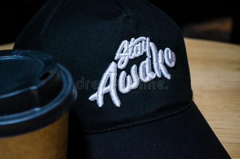 Kiev, Ukraine. 23.03.2019. An inscription and a logo on a black cap which lies on a table. Distinctive sign of local coffee shop. stock image