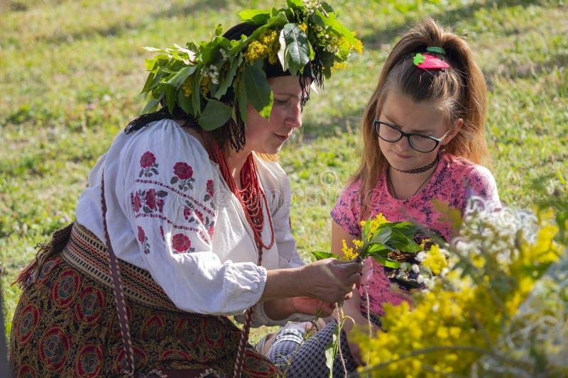 Kiev, Ukraine - 6 juillet 2017 : La femme forme une fille pour tisser une guirlande des fleurs en hommage au slave traditionnel images libres de droits
