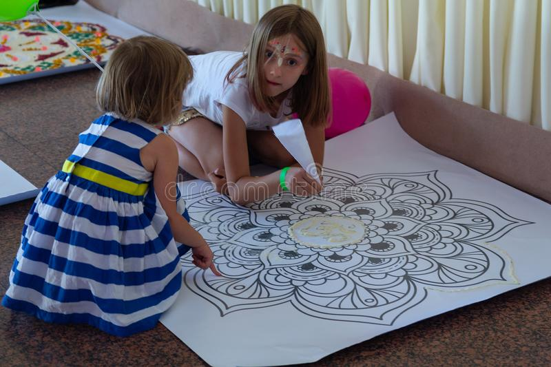 Kiev, Ukraine - July 30, 2017: Girls make a mandala from colored sand stock photo